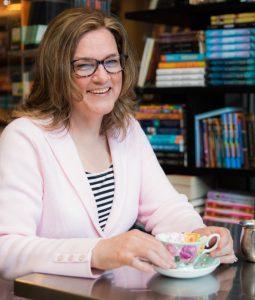 author smiling drinking tea